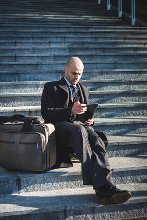 successful elegant fashionable businessman using tablet  in business district photo