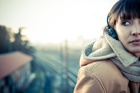 beautiful young woman listening to music headphones  in the city winter photo