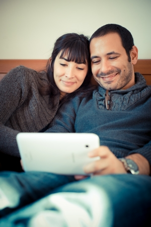 couple in love on the bed using tablet at home photo