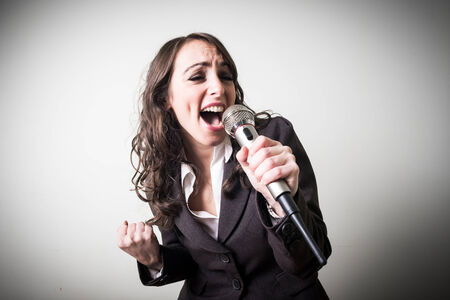 karaoke singer: singing beautiful young businesswoman on gray  Stock Photo