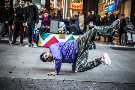 MILAN, ITALY - DECEMBER 14: breakdancers in downtown Milan on December, 14 2013: a group of performer guys breakdencers dancing in the center of Milan attracting hundreds of people  Editorial