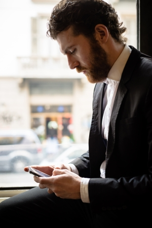 handsome bearded hipster elegant man on the cellphone photo