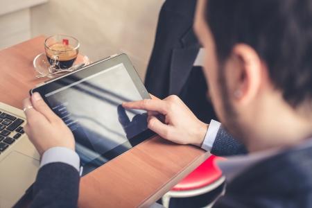 multitasking man using tablet and laptop
