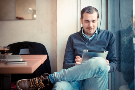 multitasking man using tablet, laptop and cellhpone connecting wifi