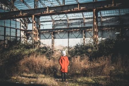 rabbit mask woman red coat winter desolate landscape Stock Photo