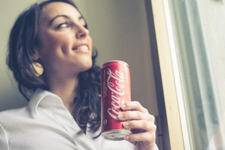 ミラノ, イタリア - 2014 年 1 月 16 日: コカ ・ コーラ瓶することができます 33 cl. コカ ・ コーラを飲む美しい女性は、世界で最も有名なブランドの清