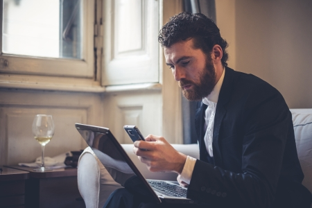 handsome bearded hipster elegant man using laptop