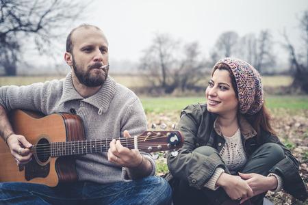 serenata: pareja de enamorados jugando serenata con la guitarra en el parque del invierno