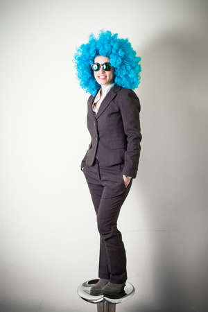funny blue wig beautiful young businesswoman on gray  photo