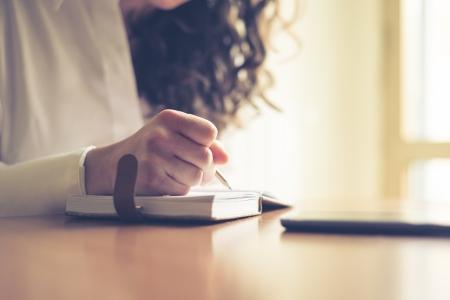 美しい女性の自宅で書くと日記とスマート フォンの操作