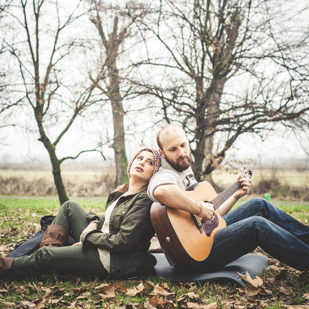 couple in love playing serenade with guitar at the park winter photo