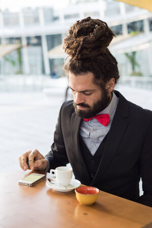 Stylish elegant dreadlocks businessman at the bar in business landscape photo
