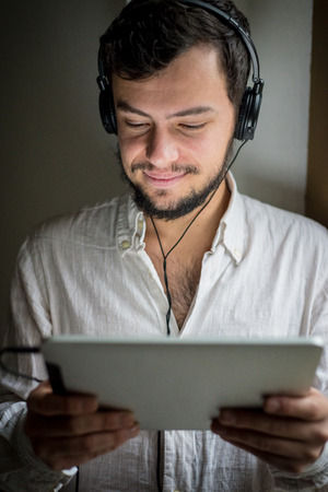 making music: young stylish man lifestyle using tablet making music at home Stock Photo