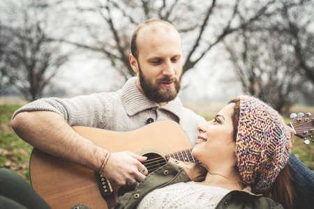 serenata: pareja de enamorados jugando serenata con la guitarra en el parque de invierno