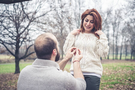 couple in love marriage proposal at the park winter photo