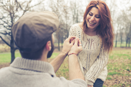 couple in love marriage proposal at the park winter