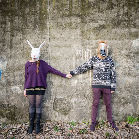 lovers park: young hipster cuople lovers rabbit and horse mask at the park