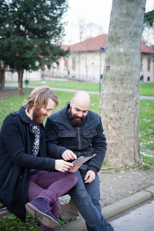 two bearded modern man working on tablet at the park Stock Photo - 26304175
