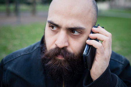 long bearded man on the phone at the park Stock Photo - 26304176