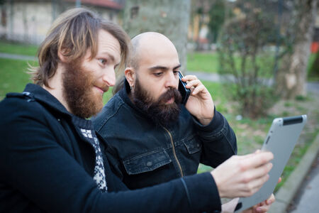 two bearded modern man working on tablet at the park Stock Photo - 26304177
