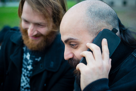 two bearded modern man working on tablet at the park Stock Photo - 26304178