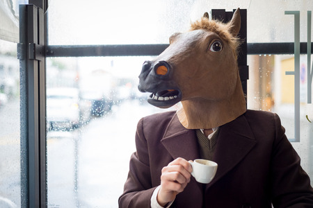 funny bearded man: young stylish man lifestyle horse mask at the bar in the city