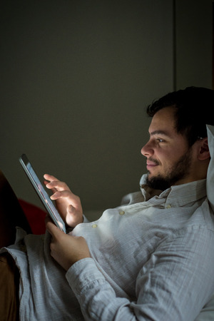young stylish man lifestyle using tablet at home photo