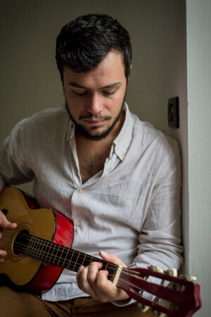 young stylish man lifestyle playing guitar at home photo