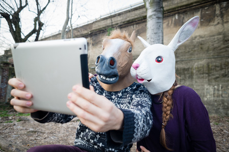 young hipster cuople horse and rabbit mask using tablet at the park Stockfoto