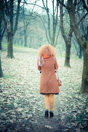 joven y bella mujer de pelo rizado de color rojo en el parque photo