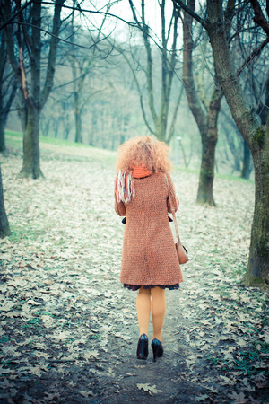 young beautiful red curly hair woman at the park photo