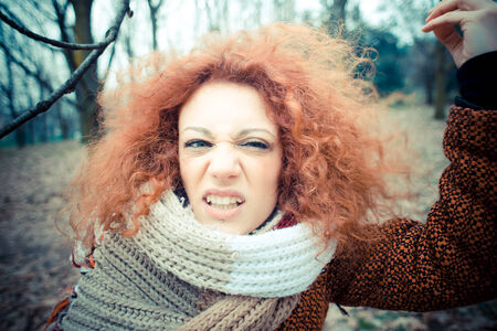 curly hair woman: young beautiful red curly hair woman at the park