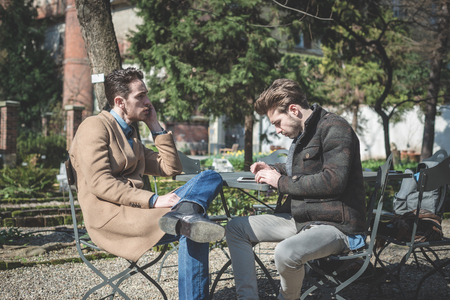 two young handsome fashion model using tablet man outdoors photo