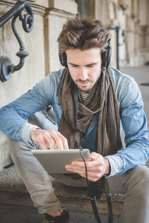 young handsome fashion model using tablet man outdoors photo