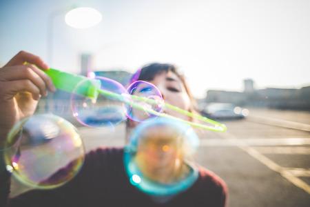 belle jeune femme hippie bulle souffleur dans la ville