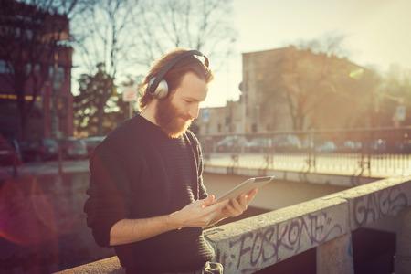 escuchando musica: hombre joven con barba elegante de escuchar música en la ciudad Foto de archivo