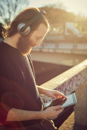 young stylish bearded man listening to music in the city photo