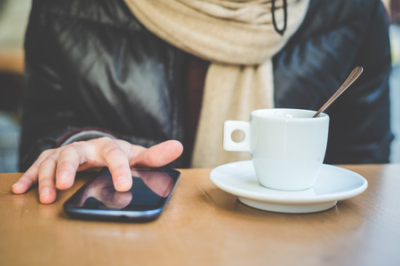 close up of woman hands with smartphone and cup of coffee at the bar photo