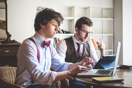 people at work: two young hipster stylish elegant men working with notebook and tablet at home