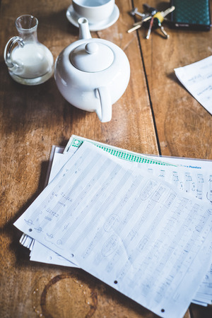 close up of sheet music and teapot on a wooden table photo