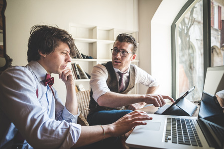 two young hipster stylish elegant men working with notebook and tablet at home
