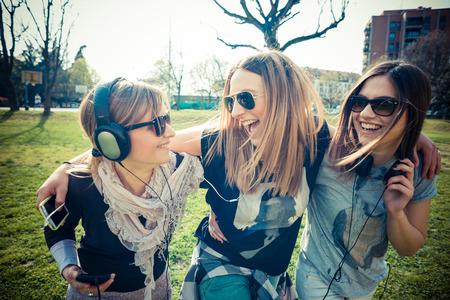 Tre belle autentici amici in contesto urbano l'ascolto di musica Archivio Fotografico - 28190970