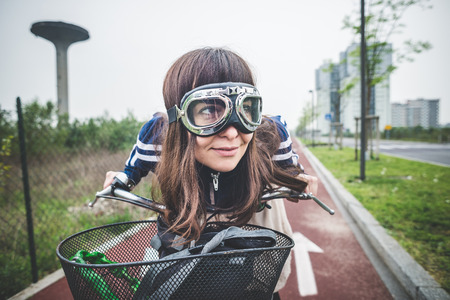 real leader: beautiful woman biker cycling in a desolate lurban landscape