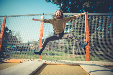 playground rides: young bearded stylish handsome hipster man jumping on trampoline at playground