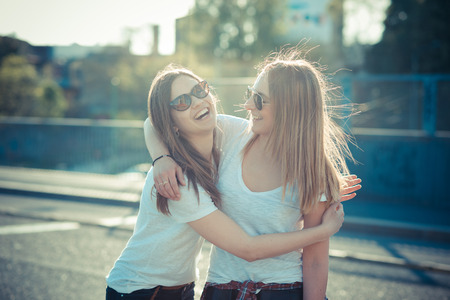 amigos abrazandose: dos hermosas mujeres jóvenes se divierten en la ciudad