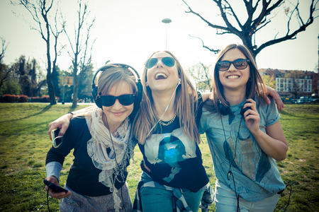 friend hug: three beautiful friends authentic in urban contest listening to music Stock Photo