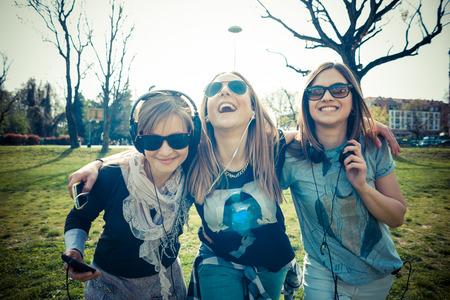personas escuchando: tres hermosas auténticos amigos en el concurso de la escucha a la música urbana Foto de archivo