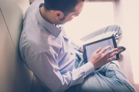 エレガントなビジネス自宅のデバイスを使用してマルチタスク マルチ メディアの男 写真素材