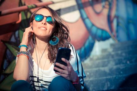 街で音楽を聴くスマートフォンを持つ若い美しいブルネットの女性