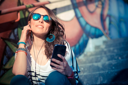 listening back: young beautiful brunette woman with smart phone listening music in the city